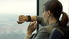Young businesswoman using smartwatch on armchair by the window in the office Stock Footage