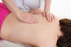 Woman is doing a salt scrub massage at spa Stock Photos