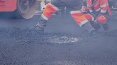 Road workers laid asphalt, repairing the road in the historic center of a Stock Footage