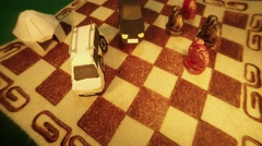 Animation of Moving on Chess Type Carpet Paper Models Cars and Figures Near Stock Footage