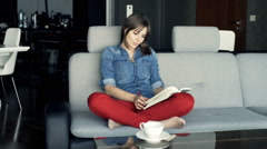 Young, beautiful woman reading book on sofa at home Stock Footage