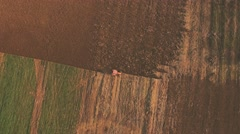 Aerial video of tractor plowing a field - stock footage