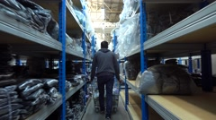 Big textile warehouse shelves and worker with cart steadicam 4K shot Stock Footage