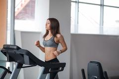 Beautiful young girl engaged in fitness in the gym. He runs on the treadmill. Stock Photos