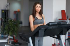 Beautiful young girl engaged in fitness in the gym. He runs on the treadmill. - stock photo