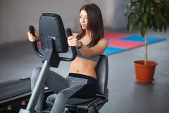 Beautiful young girl engaged in fitness in the gym. Perform cardio exercise o - stock photo