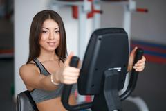 Beautiful young girl engaged in fitness in the gym. Perform cardio exercise o Stock Photos