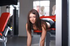 Beautiful young girl engaged in fitness in the gym. Brunette executes exercis Stock Photos