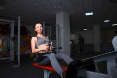 Beautiful young girl engaged in fitness in the gym. Brunette performs exercis Stock Photos