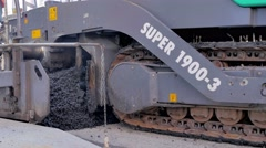 Asphalt paver machine during road construction, road construction crew apply - stock footage