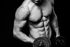 Black and white close-up of handsome power athletic mans hand stomach abs in - stock photo
