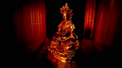 Mongolian Steel Golden Statue Spinning in Darkness on a Background of Red Stock Footage
