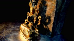 Mongolian Iron Statue With Decorative Stone Behind Spinning in the Dark Closeup Stock Footage