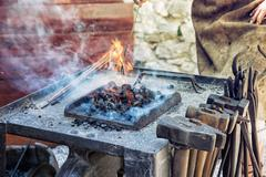 Artistic blacksmith works in the historic blacksmith workshop. Horseshoe for Stock Photos