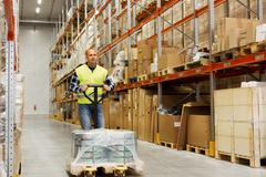 Man carrying loader with goods at warehouse Stock Photos