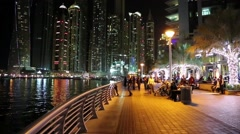 People on the waterfront, night Dubai Marina, United Arab Emirates - stock footage