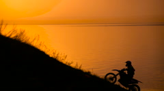 Success. motocross bike at sunset on hill climbs Stock Footage