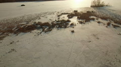 Tracks on the melting snow of a lake in spring, aerial shot Stock Footage