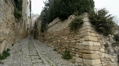 Narrow cobbled uphill street in Gordes, Provence, France, pan Stock Footage