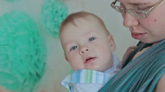 Mother holding baby in sling - stock footage