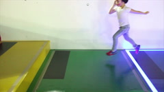People running in slow motion on colored glowing steps (side view) Stock Footage
