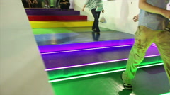Low angle Medium shot people descending multi-colored sci-fi steps - stock footage
