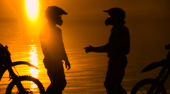 Two other motorcyclists met at beoregu river at sunset. They are happy to see Stock Footage