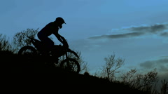Rider silhouette in the night. He goes down the hill on his extreme motocross Stock Footage
