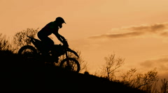 Motocross bike slides down a hill at sunset. Silhouette of the motorcyclist Stock Footage