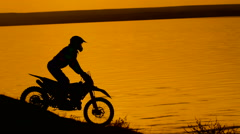 Motorcyclist silhouette at sunset. He freely travels around the sands on the Stock Footage