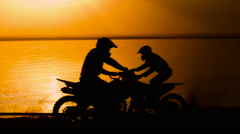 Off-road motorbike extreme cornering. Motorcyclist at sunset near the river - stock footage