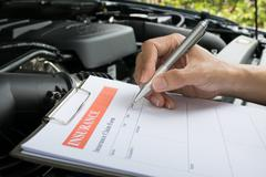 Mechanic Inspecting damage car and filling in accident report form Stock Photos