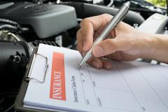 Mechanic Inspecting damage car and filling in accident report form - stock photo