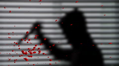 Hooded man in the shadows stabbing as blood sprays - stock footage