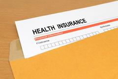 health Insurance application form on brown envelope - stock photo