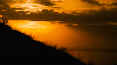 Motocross rider storms obstacle. Climb up the hill on the road. Sunset painted Stock Footage