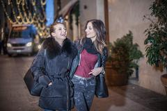 Young women walking down street in the evening arm in arm laughing Stock Photos