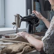 Close up of woman sewing textiles on vintage sewing machine Stock Photos
