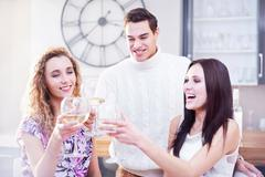 Three young adult friends making a white wine toast in kitchen Stock Photos