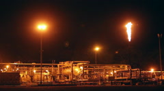 Oil well platform illuminated at night and burning off waste gas. - stock footage