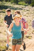 Teenage girl and adult friends running along dirt track, Bridger, Montana, US - stock photo