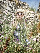 Pretty woman is afraid of insects in the field flowers on the castle ruins Stock Photos