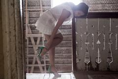 Young woman putting on heels at top of staircase Stock Photos