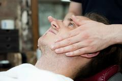 Side view of young mans head and shoulders having facial massage Stock Photos