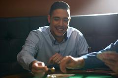 Man gambling key playing card game at pub card table - stock photo
