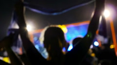 Blurred silhouettes of concert crowd in front of bright stage lights in Asia - stock footage