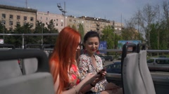 Two young pretty women taking selfie on an open top bus Stock Footage