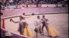 3233 matadors salute the crowd & fight bulls in arena -vintage film home movie Stock Footage