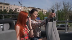 Two pretty women taking selfie on an open top bus - stock footage
