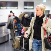 Female traveler transporting luggage in airport. Stock Photos